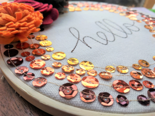 """""""Hello"""" Embroidery Hoop using sequins and felt flowers.  How to create a home decor project.  Jillibean Soup Mix the Media.  #jillibeansoup #homedecor #mixthemedia #embroideryhoop #feltflowers #sequins #diy"""
