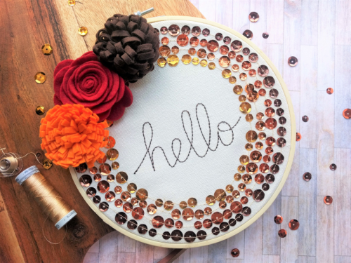 """Hello"" Embroidery Hoop using sequins and felt flowers.  How to create a home decor project.  Jillibean Soup Mix the Media.  #jillibeansoup #homedecor #mixthemedia #embroideryhoop #feltflowers #sequins #diy"