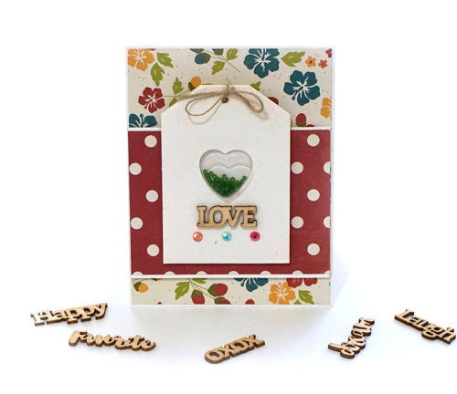 Shape shaker card using a heart shape shaker and tag, wood veneer, shaker jewels & sequins, and seed beads.  How to make a shaker card.  Jillibean Soup cardmaking.  #jillibeansoup #cardmaking #bohemianbrew #clearstamps #woodveneer